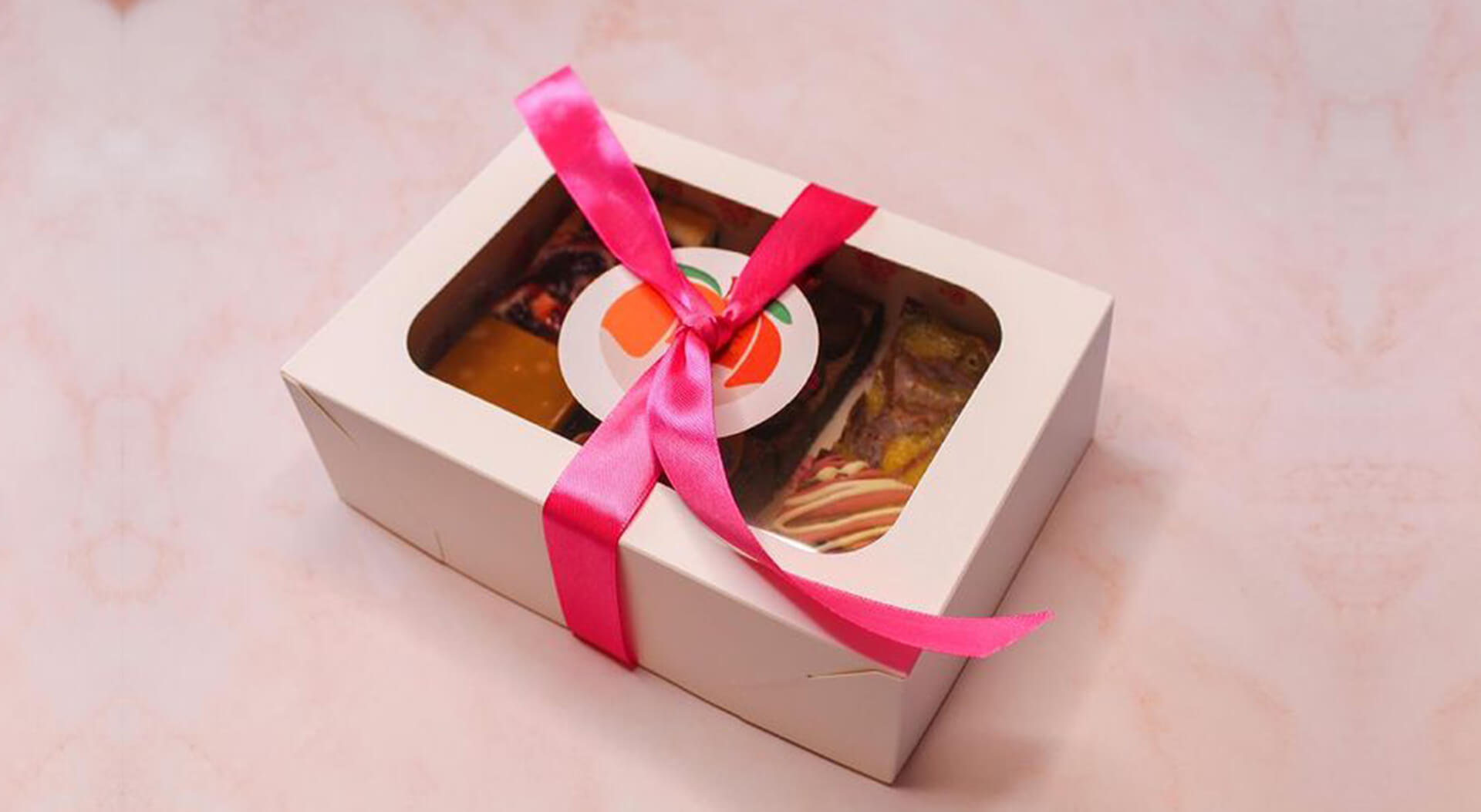 Peach Patisserie branded sticker and packaging cake box